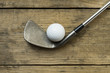 golf ball and golf club on old wood table