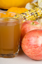 Glass of Apple Cider – A glass of apple cider. Apples, indian corn, and pumpkins in the background.