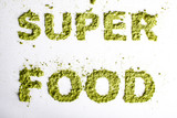 Word superfood piled of .green powder of barley grass on white background.