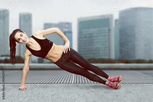Poster Woman does gymnastics in an urban setting