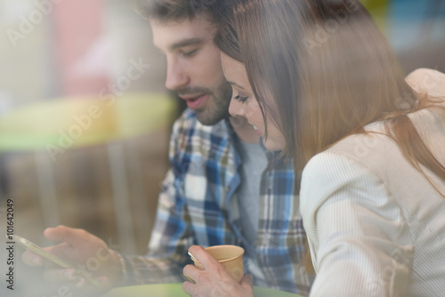 Poster Through-window view of couple sitting in coffee shop