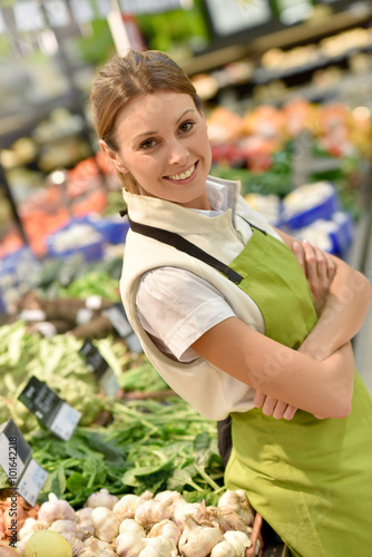 Supermarket employee with apron standing in vegetables section