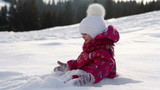 Little cute girl plays with snow