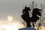 Silhouette of carved figurine on the roof and the solar disk in