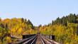 Railway tracks through colorful autumn forest in rural landscape in Saskatchewan