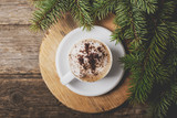 A cup of coffee with the branches of the Christmas tree on a woo