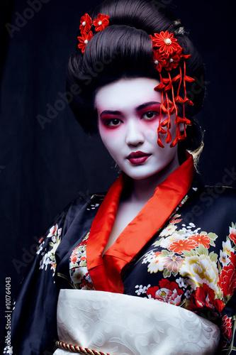 Fototapeta young pretty geisha in kimono with sakura and decoration