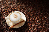 Cup of cappuccino and cinnamon on coffee beans