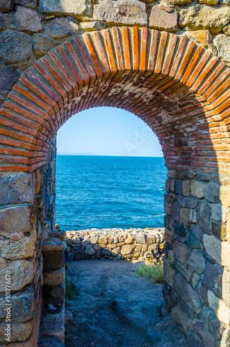 Fototapeta detail of a brick gate leading into the black sea.