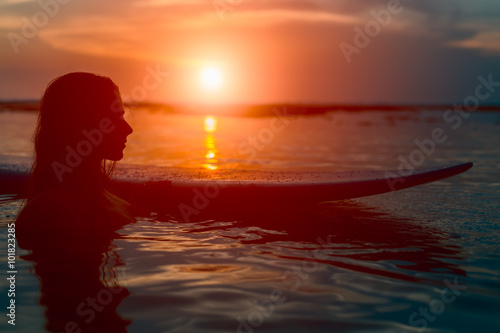 Silhouette surfer woman with surfboard at sunset Poster