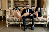 Fashion photo romance of sexy lovers couple. woman with black curly hair in black underwear and man wearing suit