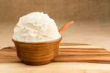 Shea butter in the wooden bowl stands on the wooden board, on th