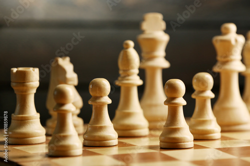 Chess pieces and game board on wooden background © Africa Studio
