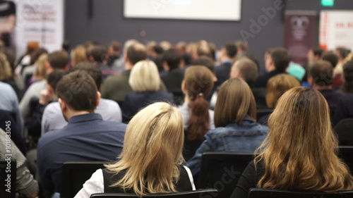 women listen to the seminar or lecture in a classroom or a large hall. female