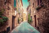 Wąska ulica w starym włoskim mieście Pienza. Toskania, Włochy. Zabytkowe