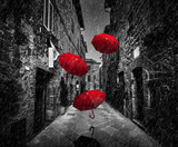 Fototapety Umrbellas flying with wind and rain on dark street in an old Italian town in Tuscany, Italy