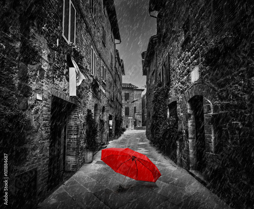 Umbrella on dark street in an old Italian town in Tuscany, Italy. Raining.
