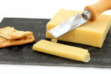 Fresh cut cheddar cheese with crackers on a slate board