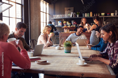 Naklejka Interior Of Coffee Shop With Customers Using Digital Devices