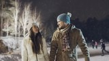 Tilt up of romantic young couple skating at outdoor rink holding hands in snowy winter evening
