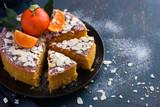 tangerine and almond cake on dark blue background,