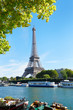 Eiffel tower and Seine river view with green tree branches in a sunny summer day