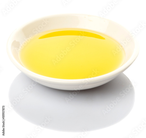 Olive oil in a white bowl over white background
