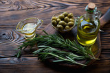 Fresh rosemary and olive oil in a rustic wooden setting, closeup