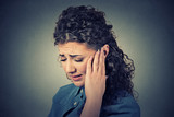 Tinnitus. Closeup sick female having ear pain touching painful head