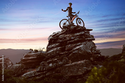 Happy biker on a big rock Poster