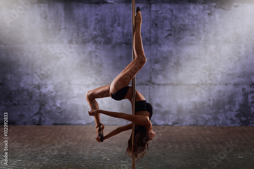 pole dance performing Beautiful woman Shot with industrial concrete background.