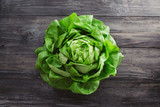 Single lettuce head over rustic wooden background - 102117843