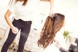 Fryzjer rozpyla lakier na włosy klientki