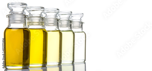 Avocado fruit oil, sesame seed oil, olive oil, grape seed oil and corn oil in vial glass bottle over white background