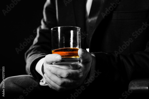 Closeup of serious businessman holding  whiskey illustrate executive privilege concept.