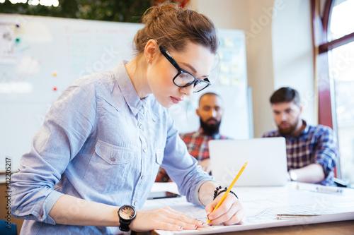 Woman engineer working on blueprint