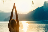 Fototapety Saluting to the sun. Young woman doing yoga by the lake at sunset
