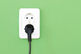 European white electrical outlet socket and black cable pluged i
