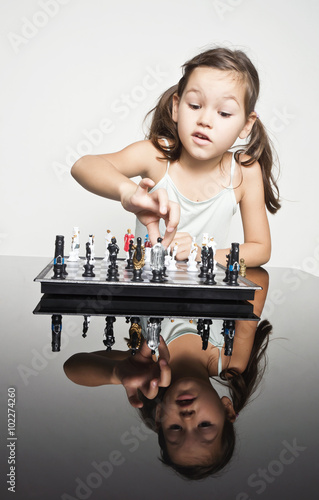 Adorable little girl concentrated playing chess Poster
