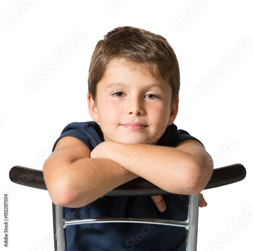 The seven year old boy sits astride a chair Poster