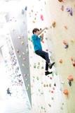 Bambino che scala una parete per arrampicata