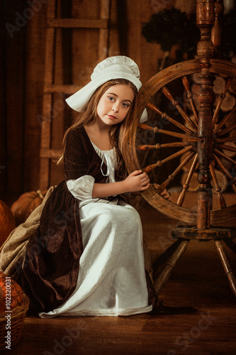 Plakat little girl in the image of Cinderella sits near a spinning wheel from the hands , hip toning , happy childhood