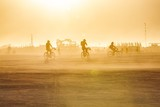 Fototapety Friends riding with bikes in Burning Man festival on a warm sunny day