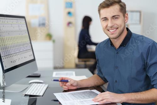 mata magnetyczna lächelnder mitarbeiter im büro arbeitet am pc