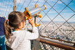 Little girl using the telescope in the Eiffel Tower