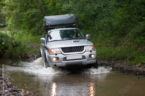 Poster BOLSHOY KAMEN, RUSSIA - AUGUST 03, 2015: SUV is crossing a river