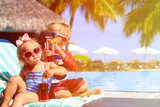 kids relax on tropical beach resort and drink juices