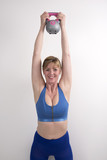 Woman using a 2 kg weight kettle bell to exercise