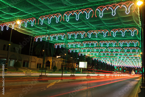 Street in Muscat decorated with lights плакат