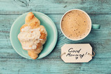 Fototapety Coffee mug with croissant and notes good morning on turquoise rustic table from above, cozy and tasty breakfast, vintage toned